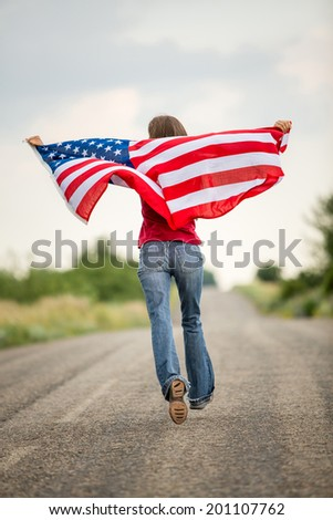 Patriotic young woman with the American flag held in her outstretched hands running along the road in motion. focus on flag - stock photo