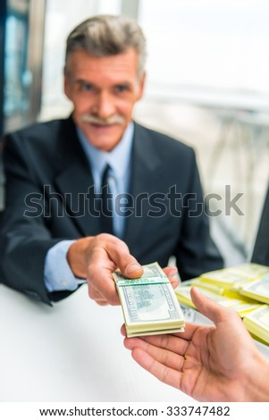 Patron. Senior male businessman gives money for the hospital - stock photo