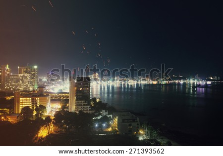 Pattaya City and Sea in Twilight,  Thailands traditional Loy Krathong Festival. Sky lanterns in the sky - stock photo