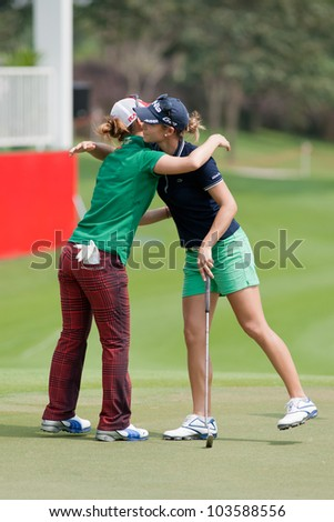 PATTAYA, THAILAND-FEBRUARY 16: Azahara Munoz of Spain (R) thanks another golfer after finish hole 18 on Day 1 of Honda LPGA 2012 on February 16 2012 at Siam Country Club Old Course in Pattaya Thailand