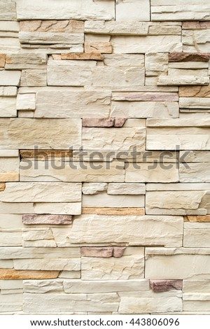 Pattern of decorative cream color rough stone wall background texture - stock photo