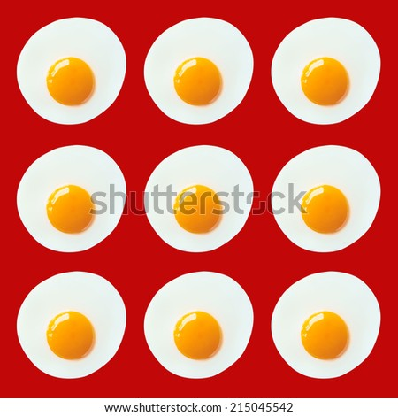 Pattern of fried eggs on red background - stock photo