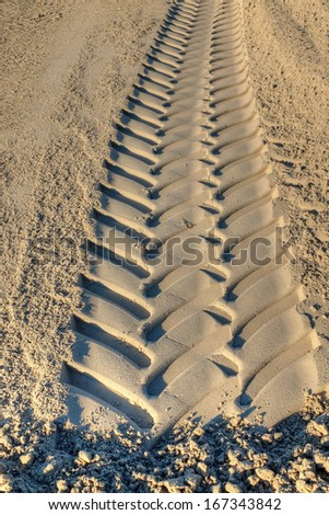pattern of tire tracks in soft sand - stock photo