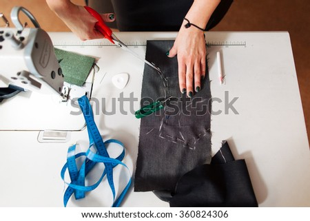 pattern, scissors, tape measure, and a sewing machine. Workplace of seamstress. Dressmaker cuts dress detail on the sketch lines. - stock photo