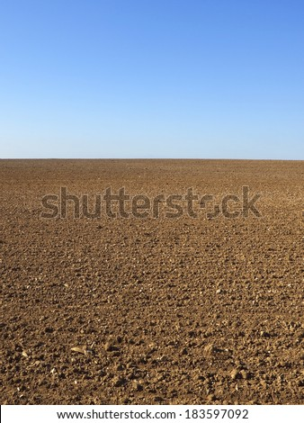 patterns and textures of newly rolled brown soil with blue sky above