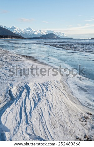 Patterns in wind blown snow beside a frozen Alaskan river. - stock photo
