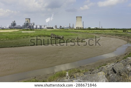 Paull, Holderness, Yorkshire, UK. Hedon Haven at low tide, and the large chemical plant in the background with a rotting wooden boat on the mud bank near Paul, East Riding of Yorkshire, UK. - stock photo