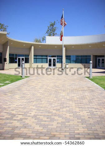 paved building entrance with american and california flag - stock photo