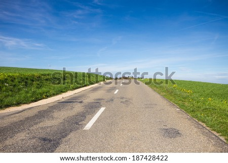 Paved road in a landscape with green field and blue sky - stock photo