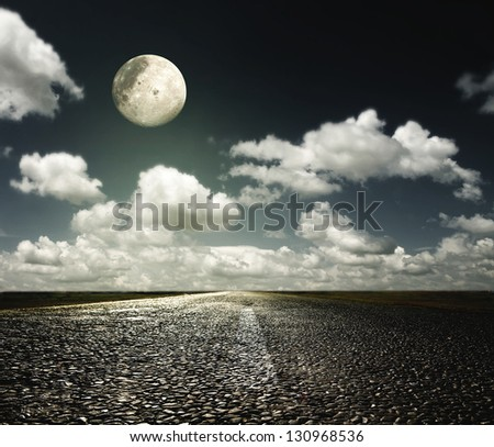 paved road in the night sky with the moon - stock photo