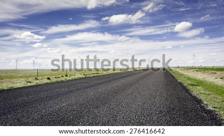 Paved road leads through an Idaho wind farm - stock photo