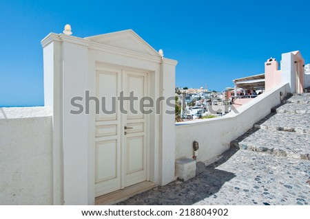 Paved street with the houses carved into the rock on the edge of the caldera cliff in Fira town. Thira (Santorini), Greece. - stock photo