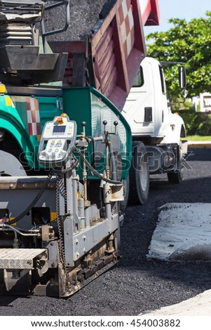 Pavement truck laying fresh asphalt  during road construction