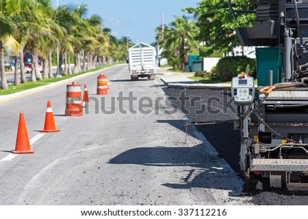 Pavement truck laying fresh asphalt  during tropical road construction   - stock photo