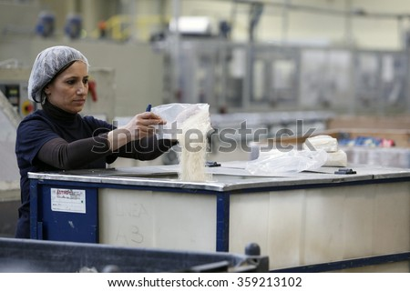 PAVIA, ITALY - 16 APRIL 2012: An employee empties out packets of damaged white rice at a rice processing and packaging plant in Pavia, Italy. - stock photo