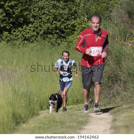 PAVIE, FRANCE - MAY 18: A dog leads a runner who is visually impaired on a countryside path at the Trail of Pavie, on May 18, 2014, in Pavie, France.  - stock photo