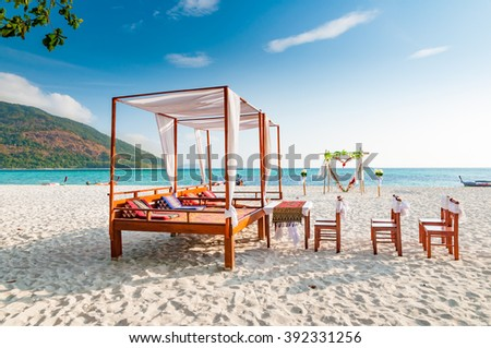 Pavilion chairs and wedding arch setup on the beach in a sunny blue sky day - stock photo