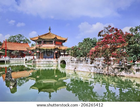 Pavilion mirrored in green pond, Yuantong Temple, Kunming, Yunnan Province, China. - stock photo