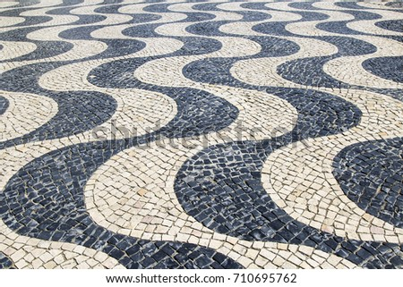 Paving stone with ornament as a sea wave, the picture was taken in Cascais, Portugal