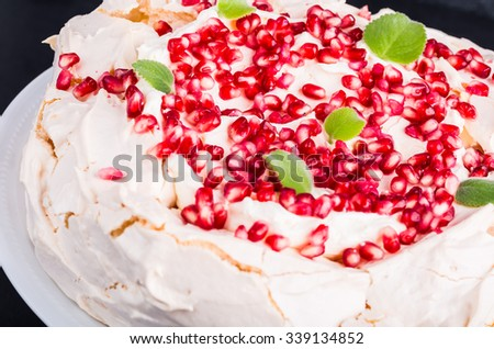 Pavlova cake with pomegranate and fresh mint leaves on white plate - stock photo