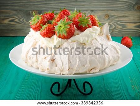 Pavlova cake with strawberry on rustic background - stock photo