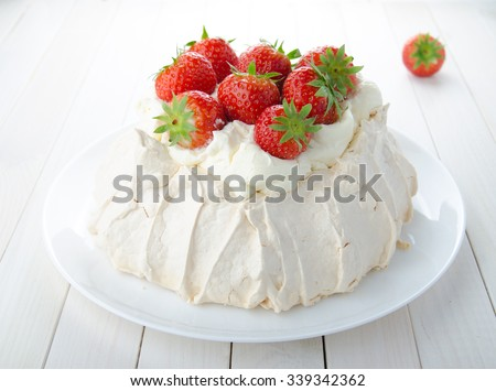 Pavlova cake with strawberry on rustic background