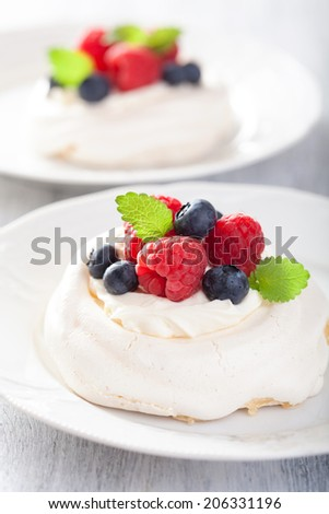 pavlova meringue cake with cream and berry