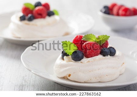 pavlova meringue cake with cream and berry  - stock photo