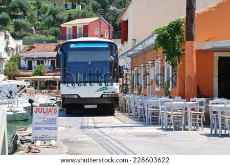 PAXOS, GREECE - JUNE 14, 2014: The local island bus negotiates the narrow seafront road at Loggos on the Greek island of Paxos. Taverna diners have to vacate their seats to allow the bus to pass. - stock photo