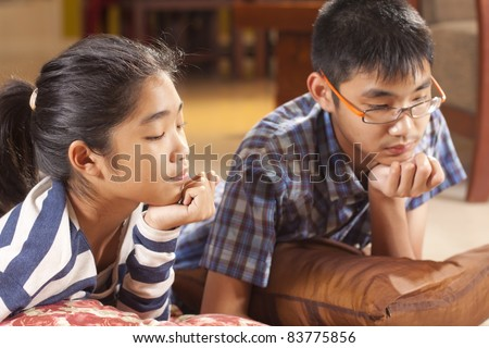 pay attention, brother and sister paying attention to study. - stock photo