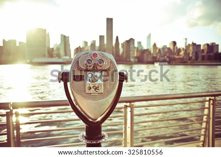 Pay binoculars in Long Island City with the Manhattan skyline in the background. travel, vacation, sightseeing, new york, tourism, and urban living concept
