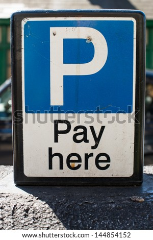 Pay Here signboard on top of an exterior wall with parked cars visible behind, closeup view - stock photo