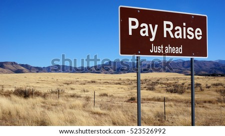 Pay Raise road sign with blue sky and wilderness