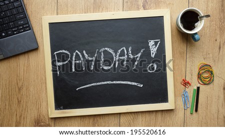 Payday written on a chalkboard at the office - stock photo