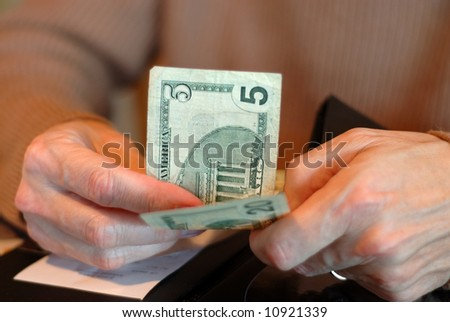 Paying The Bill With Twenty Five Dollars - Male hands holding a five and a twenty dollar bill and the check.  Shallow dof. - stock photo