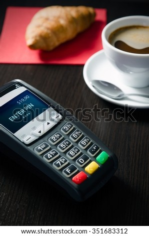 Payment terminal in restaurant. Croissaint and coffee in background - stock photo