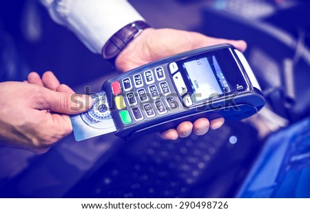 Payment with credit card - man put the credit card into a reader with blue color tone effect