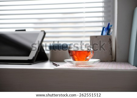 PC tablet, notebook and cup of tea on windowsill. Working place concept - stock photo