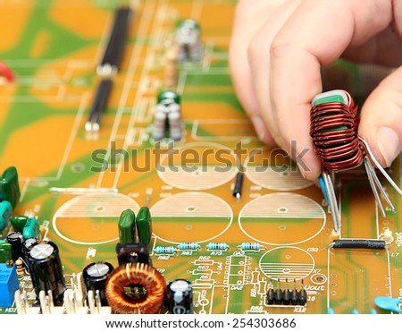 PCB mounting by human hands. In manual soldering TECHNOLOGIES th - stock photo