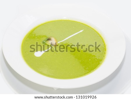 pea soup decorated with mushrooms and green on a white plate in a restaurant