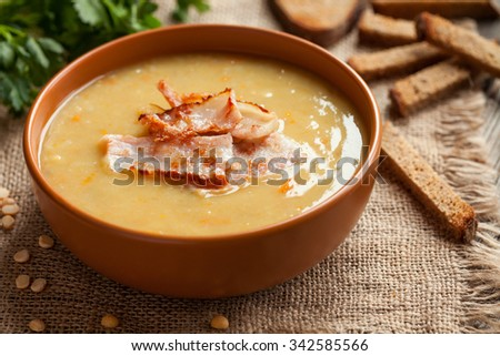 Pea soup traditional homemade german recipe in clay dish with greens and croutons on vintage wooden table background. Rustic style - stock photo