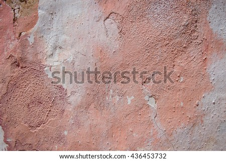 peace of wall with damaged pink plaster as a background in pastel colors