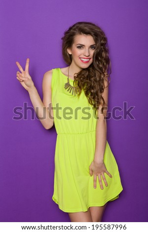 Peace sign. Beautiful young woman showing victory hand, peace sign. Three quarter length studio shot on violet background. - stock photo