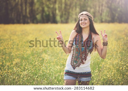 Peace sign from smiling hippie in a meadow. Freedom and harmony - stock photo