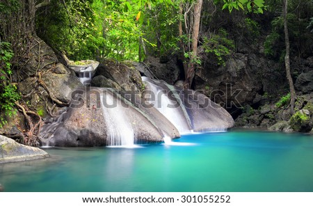 Peaceful and relaxing landscape background of tropical forest with small beautiful waterfall flowing from wet stones and rocks and falling in blue water lake  - stock photo