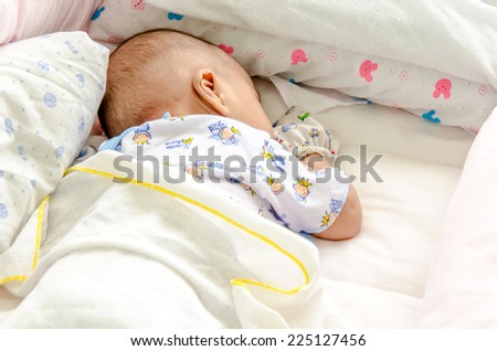 Peaceful baby lying on a bed while sleeping in a bed room - stock photo