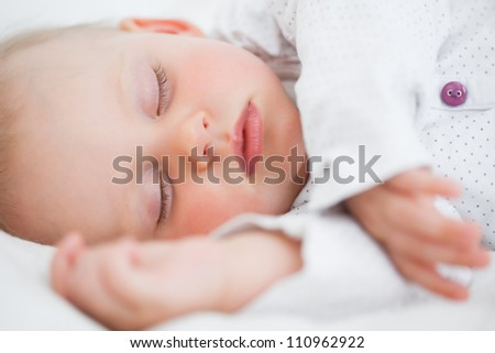 Peaceful baby lying while falling asleep in a bedroom - stock photo