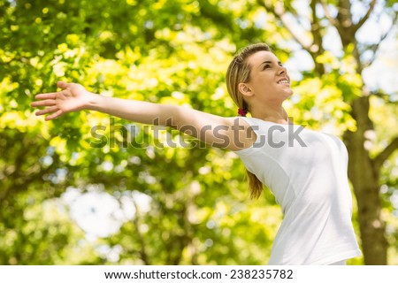 Peaceful blonde doing yoga in the park on a sunny day - stock photo
