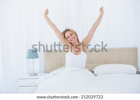 Peaceful blonde woman stretching in bed at home in the bedroom - stock photo