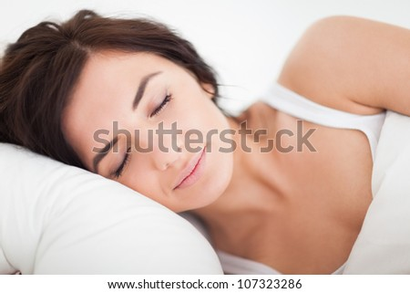 Peaceful brown-haired woman sleeping in the bed in a bright bedroom